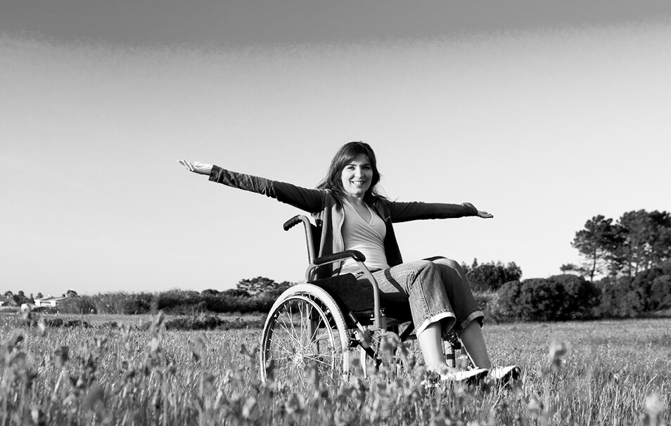 Woman sitting in a wheel chair in a field